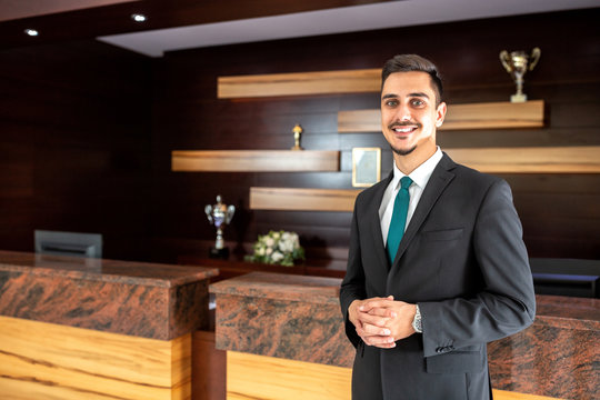 Smiling hotel worker welcoming guests
