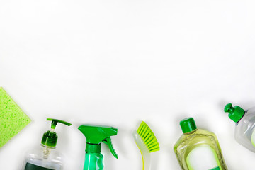 Detergents in green plastic bottles for housekeeping. Сleaning accessories. Top view of cleaning supplies on white background. Close up.