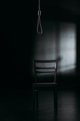 chair under hanging rope noose on black background with lighting, suicide prevention concept