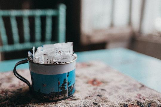A mug full of sugar packets