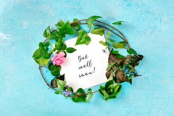 Get well soon card with a wreath of green ivy leaves and a tender pink rose, overhead shot on a blue background