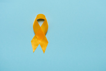 top view of yellow awareness ribbon on blue background, suicide prevention concept