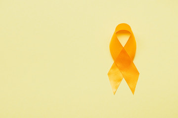 top view of yellow awareness ribbon on yellow background, suicide prevention concept