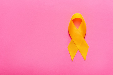 top view of yellow awareness ribbon on pink background, suicide prevention concept