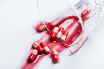 overturned glass and wet pills in red spills of water on white background, suicide prevention concept