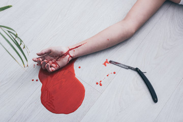 partial view of lifeless woman with cut bleeding veins lying on bed near straight razor and puddle of blood on floor
