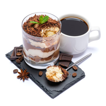 Classic tiramisu dessert in a glass cup and pieces of chocolate on stone cutting board on white background with clipping path