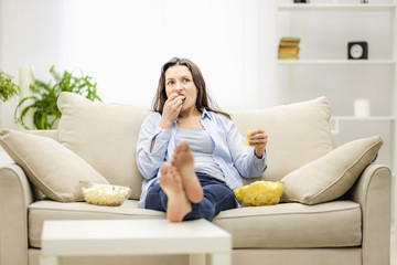 Portrait of pretty, charming, cheerful woman with straight black hair, who is eating pop corn and potato chips, watching comic serial, comedy, sitting with crossed legs in living room.