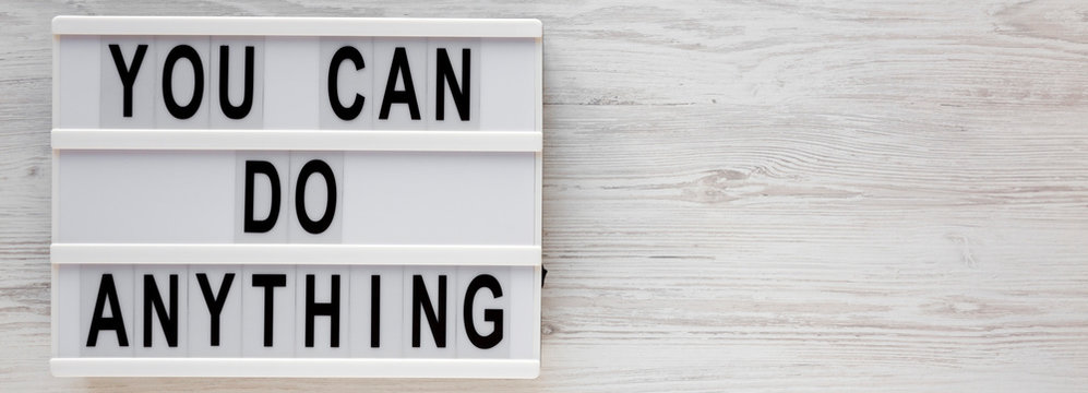 'You can do anything' words on a lightbox on a white wooden background, top view. Overhead, from above, flat lay. Copy space.