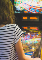 Little girl playing pinball game in theme park.