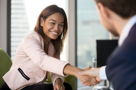 Smiling African American businesswoman shaking hand of businessman