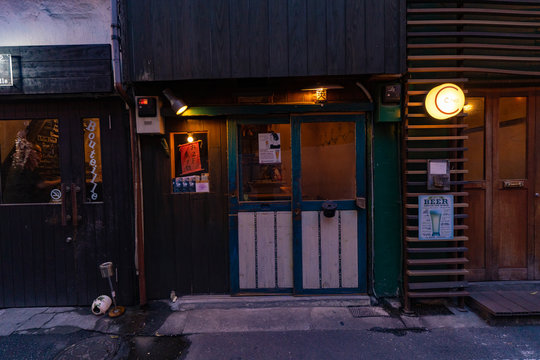 TOKYO, JAPAN - July 2018 - Golden Gai Bars Street. Exterior view with Japanese people drinking inside the bar.
