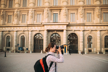 Stockholm, Sweden. Young Adult Caucasian Woman Lady Tourist Traveler Photographer Taking Pictures Photos Near Stockholm Palace. Royal Palace In Old Town Gamla Stan. Famous Popular Place. UNESCO.