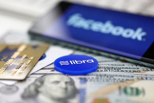 Blue chip with libra sign lying on big pile of US dollars