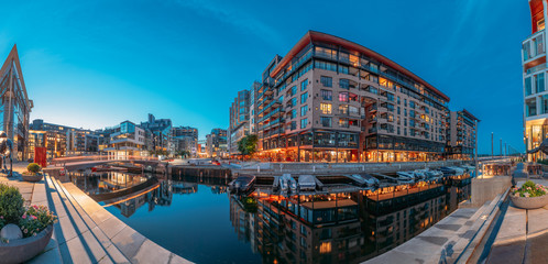 Oslo, Norway. Night Embankment And Residential Multi-storey Houses In Aker Brygge District. Summer Evening. Residential Area Reflected In Waters. Famous And Popular Place. Panorama, Panoramic View.