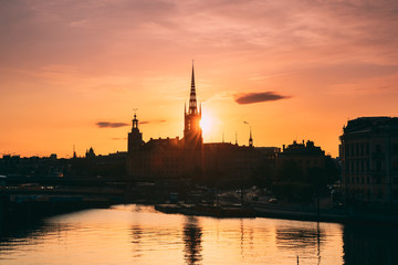 Stockholm, Sweden. Sunset Sun Shine Through Dark Silhouette Of Riddarholm Church In Stockholm Skyline. Scenic View Of Gamla Stan Old Town In Dramatic Sunshine Sunlight. Famous Popular Destination
