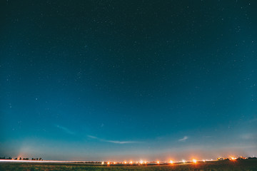 Night Starry Sky With Glowing Stars Above Landscape With City Lights. Night Starry Sky Above Ground. Copy Space