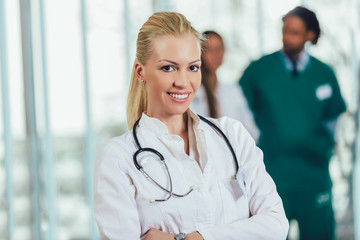 Portrait of attractive female doctor on hospital corridor looking at camera smiling.