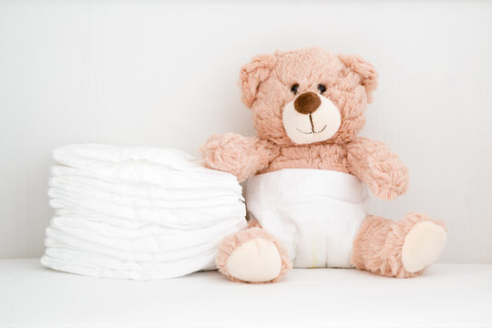 Brown teddy bear sitting in baby bed. Stack of white diapers. Front view. Closeup.