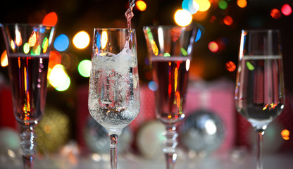 Beautiful splash of champagne glasses and Christmas lights