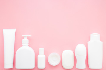Different white toiletries on pastel pink table. Care about face, hands, legs and body skin. Women beauty products. Empty place for text or logo. Flat lay. Top down view. Closeup.
