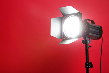 Studio lighting with tripod on red background