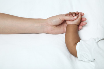 Mother hand holding baby girl hand on white bed