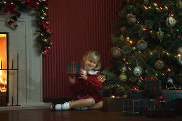 portrait of little girl with gift box in  christmas domestic environment