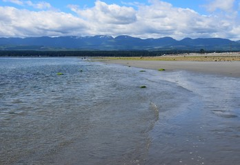 landscape during low tide at Goose Spit Park beach, Comox Vancouver Island, BC Canada; view to the West
