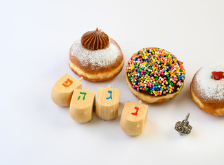 Fresh   donuts  and wooden dreidels for Hanukkah celebration. Hebrew letters on color dreidels say : Great Miracle Happened Hear.