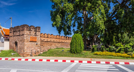 Photo Stands Old building Tha Phae Gate Chiang Mai old town city and street ancient wall at moat (Chiang Mai Gate) is a major tourist attraction in Chiang Mai Northern Thailand.blue sky