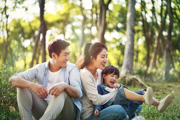 asian family with one child relaxing outdoors