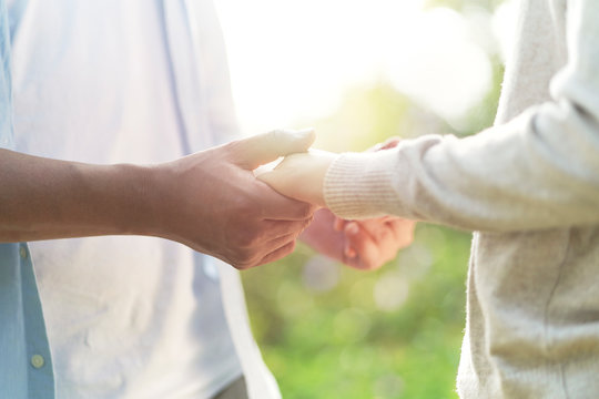 young asian couple holding hands outdoors
