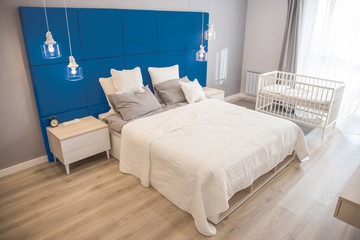 Interior of the room in light colors. Bedroom with a bed and a cot in colors classic blue 2020