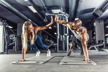 Poster Fitness Sport couple doing plank exercise workout in fitness centrum. Man and woman practicing plank in the gym