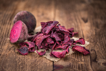 Beetroot Chips on an old wooden table (selective focus)
