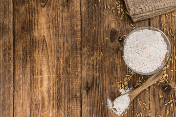 Some fresh Oat Flour on wooden background (selective focus; close-up shot)