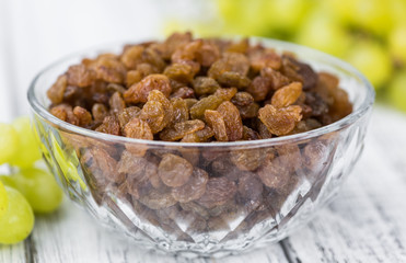 Portion of healthy Raisins on an old wooden table (selective focus; close-up shot)