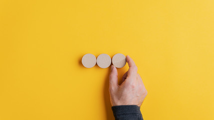 Placing three blank wooden cut circles in a row