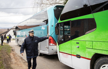 Police secure buses with migrants near migrant camp in Vucjak