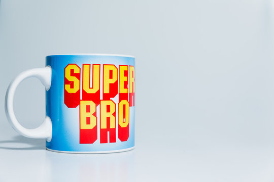 London, England, 24/10/2019 Super Bro mega mug on isolated white background lit professional in studio. Type in text font like mario or other retro games even superman comic book style