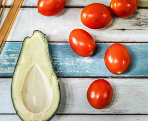 Tomatoes, avocado on a wooden table seen from above