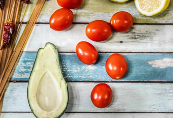 Tomatoes, avocado, spaghetti, lemon and chili peppers on a wooden table