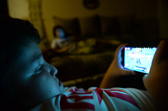 online game children addiction of small fat kid playing smartphone at home lying lazy