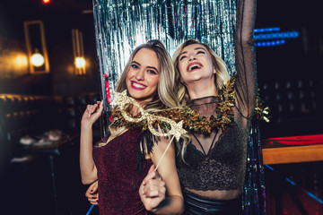 Girls celebrating new years eve at the nightclub. Group of female friends partying in pub