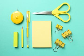 Yellow color school supplies arrangement on green background
