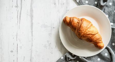 Słodkie ciastko croissant na białym drewnianym tle
