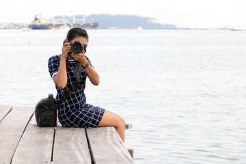 A young woman with camera sitting on a wooden pier. Tourist takes pictures on mole over sea.