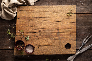 Chopping board on dark, wooden table. Rosemary, pepper, salt. Copy space. Wall mural