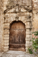 An old wood door in a majestic stone entry is closed in the village of Gordes in southern France.